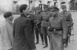 German officer (possibly SS General Maximilian von Herff) questioning Jews in Warsaw, Poland, 14-15 May 1943; note Jürgen Stroop (with goggles) and Karl Kaleske (or Erich Steidtmann; first from right) in background