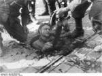 Polish insurgent fighter surrendered from his position in the sewers under Warsaw, Poland, 27 Sep 1944, photo 1 of 2; note MP 40 submachine gun