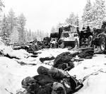 Column of Russian vehicles driving by dead Russian soldiers, Battle of Raate Road, Jan 1940