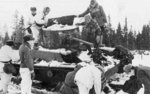 Finnish troops inspecting a wrecked Soviet T-26 tank after the Battle of Raate Road, Finland, Jan 1940