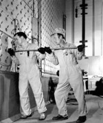 Workers using a rod to push uranium slugs into the loading face of the X-10 graphite reactor, Oak Ridge, Tennessee, United States, date unknown