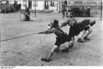 Hitler Youth members playing tug of war while donning helmets and gas masks, 1933