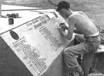 Staff Sergeant Marvin Culbreth of 13th Bomb Squadron of USAAF 3rd Bomb Group lettering a memorial to fallen comrades at an airfield at Port Moresby, Australian Papua, 1943
