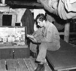 USAAF 3rd Bomb Group photographer Jack Heyn reading at his bunk, Dobodura Airfield, Australian Papua, mid-1943