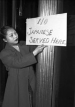 Chinese-American Gertrude Moy posting anti-Japanese sign outside the Hoe Sai Gai restaurant where she was employed, Chicago, Illinois, United States, Dec 1941