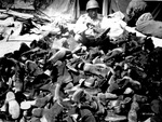 US Army 3278th Quartermaster Company African-American Private Robert Askew examining a pile of overshoes, 8 Apr 1944