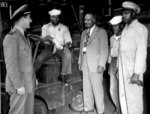 Lester Granger chatting with African-American US Navy S1/c Rofes Herring, S2/c Walter Calvert, and civilian Nollie H. Million, 20 Jun 1945; the officer was identified as Lt Roper