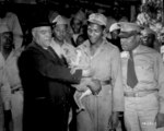 Bishop John Andrew Gregg of African Methodist Church in North Central United States playing with a koala bear while African-American US Army soldiers looked on, Australia, 21 Jul 1943