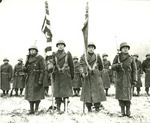 Japanese-American color guard of the US 442nd Regimental Combat Team standing at attention while citations are read following the fighting in Bruyeres, France, 12 Nov 1944