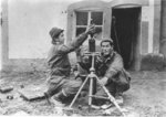 Japanese-American troops of US 442nd Regimental Combat Team firing a round of mortar, Saint-Dié-des-Vosges, France, circa late 1944