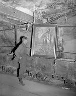 US Army Corporal Donald Ornitz examining a looted painting in the Merkers salt mine, Germany, Apr 1945