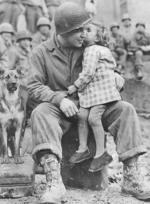 US Army Signal Corp Photo Tec-4 Elvin Harley getting a kiss from a French child while listening to the US 9th Armored Division Band near Aboncourt, France, 14 Feb 1945