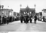 Uniformed German guards marching down Unter den Linden during the Summer Olympics in Berlin, Germany, Aug 1936; note Brandenburg Gate in background