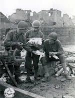 US Army Pfc. Carl Anker, Pfc. Edmund Dill, and Sgt. Ted Bailey sharing the contents of the care package sent by Dill