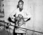 US Navy African-American Seaman 1st Class E. Perry splacing steel cable, 17 May 1945