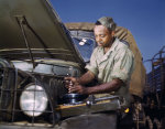 African-American mechanic in the US Army maintaining a truck, Fort Knox, Kentucky, United States, Jun 1942, photo 1 of 2