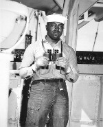 US Navy African-American Seaman 2nd Class Napoleon Reid standing on lookout on a ship in the Pacific Ocean, 19 Mar 1945