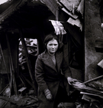 A British girl before a V2 rocket-damaged building, Battersea, London, England, United Kingdom, 27 Jan 1945