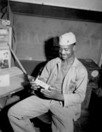 African-American US Marine 4th Ammunition Company Private First Class Luther Woodward admiring his Bronze Star medal, 17 Apr 1945; his award was later upgraded to the Silver Star