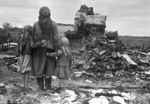 Russian mother and children looking at a destroyed home, Russia, 1 Sep 1943
