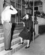 WAVES Ensign Emma D. Shelton received salute from a US Marine sentry s she enters an apartment building that served as temporary WAVES quarters, circa 1943