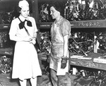 US Navy WAVES Captain Mildred McAfee listening to Storekeeper 2nd Class Dorothy Oates, Naval Air Station Pearl Harbor, US Territory of Hawaii, 4 Jul 1945