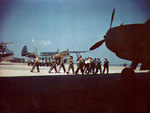 WAVES and Women Marines mechanics marching, Naval Air Station, Norfolk, Virginia, United States, circa 1944-1945; note PBM-3D, OS2U, and TBM aircraft