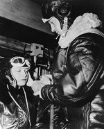 US Navy sailor helping a WAVES trainee pilot putting on her oxygen mask,  Naval Air Station, Jacksonville, Florida, United States, 15 Oct 1943