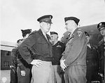 Dwight Eisenhower and Lucius Clay at the airfield in Gatow, Berlin, Germany, 20 Jul 1945; note Omar Bradley in background