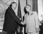 Secretary of the US Navy William B. Franke congratulating Admiral Arleigh A. Burke on his third term as Chief of Naval Operations, Aug 1959