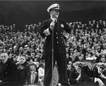 Admiral Burke addressing an US Naval Academy pep rally, 23 Nov 1960, on the eve of the Army-Navy football game