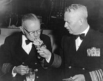 Admiral Burke lighting a cigarette for Fleet Admiral Halsey, probably New York City, circa mid- or late-1950s