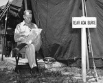 Rear Admiral Burke reading outside his tent at the United Nations