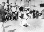 Ensign Burke pushing a peanut by blowing on it during a shipboard competition aboard USS Arizona, circa 1923-1925