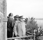 Winston Churchill and American generals on a balcony watching Allied vehicles crossing the Rhine River into Germany, 25 Mar 1945