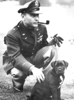 Brigadier General Ira Eaker in Britain, playing with a dog, 1942-1944
