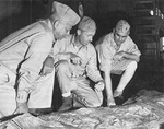 Major General Roy Geiger, Colonel Merwin Silverthorn, and Brigadier General Pedro del Valle studying Guam terrain aboard USS Appalachian, mid-1944
