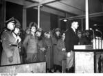 The one millionth German resettler of Wartheland speaking at a ceremony, Posen, Germany, 16 Mar 1944; Arthur Greiser and Walter Petzel in background