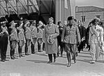 Adolf Hitler and Benito Mussolini walking in front of saluting military during Hitler