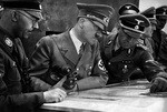 A German SS-Standartenführer showing troop dispositions on a map to Himmler and Hitler, 1939