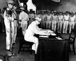 MacArthur signing Japanese surrender aboard USS Missouri, 2 Sep 1945, photo 1 of 4