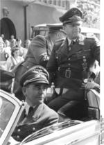 German Minister of Armaments Albert Speer (front) and Field Marshal Erhard Milch (rear) in an automobile en route to inspect a defense plant, Germany, May 1944