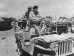 General Bernard Montgomery of UK 8th Army in Sicily, Italy, Jul or Aug 1943; note Willys MB and two GMC DUKW vehicles