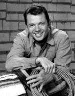 Audie Murphy as his character Tom Smith from the television show Whispering Smith, 1959