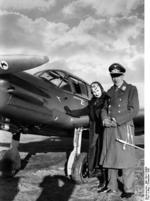 German Luftwaffe Lieutenant Colonel Theodor Osterkamp and his wife posing with a Me 108 Taifun aircraft, Dec 1938
