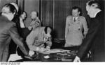 Adolf Hitler signing the Munich Agreement, Germany, 30 Sep 1938; note Joachim von RIbbentrop, Benito Mussolini, and Julius Schaub in background