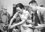 Song Meiling helping with bandaging a wounded Chinese soldier, circa 1932