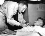 Vice Admiral Raymond Spruance awarding Purple Heart to USMC Corporal John K. Galuszka aboard a hospital ship, Pearl Harbor, Hawaii, 17 Dec 1943. Corporal Galuszka had been wounded during the Gilberts Operation.
