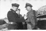 SS-Sturmbannführer Schöneberger and SS-Obersturmbannführer Max Wünsche (background) awarding a man under their command, near Kharkov, Ukraine, Mar 1943