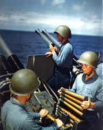 Crew of a 40mm quad anti-aircraft machine gun mount of Alaska loaded clips into the loaders of the left pair of guns, off Iwo Jima, 6 Mar 1945